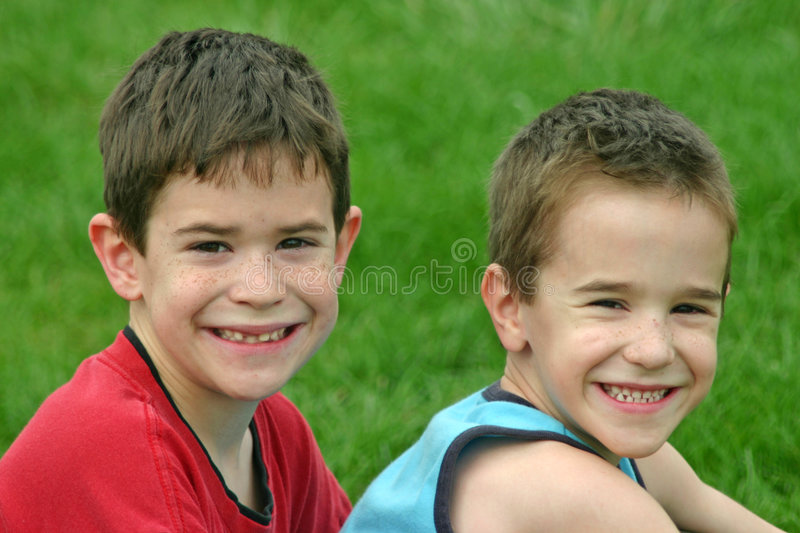 Brothers Smiling. Against a Green Grass Background stock image