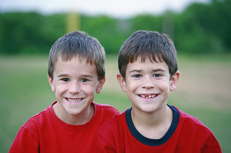 Brothers Smiling. Two Brothers Smiling outdoors each wearing red royalty free stock photo