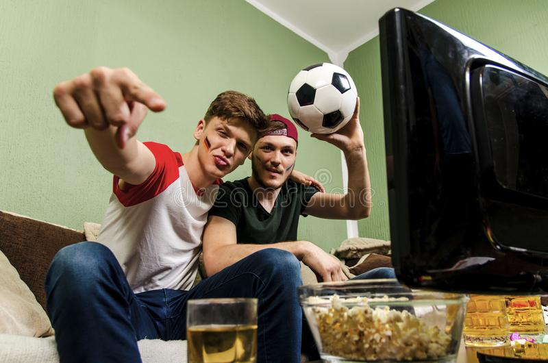 Brothers soccer fans with face paint cheering in front of TV stock photo