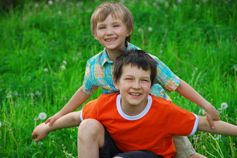 Brothers together in field. A view of two happy brothers playing in an open field of lush green grass and dandelions stock photos