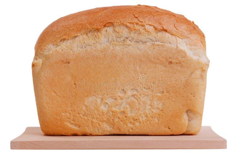 Brotlaib auf dem Schneidebrett lokalisiert auf weißem Hintergrundlaib lizenzfreie stockfotografie