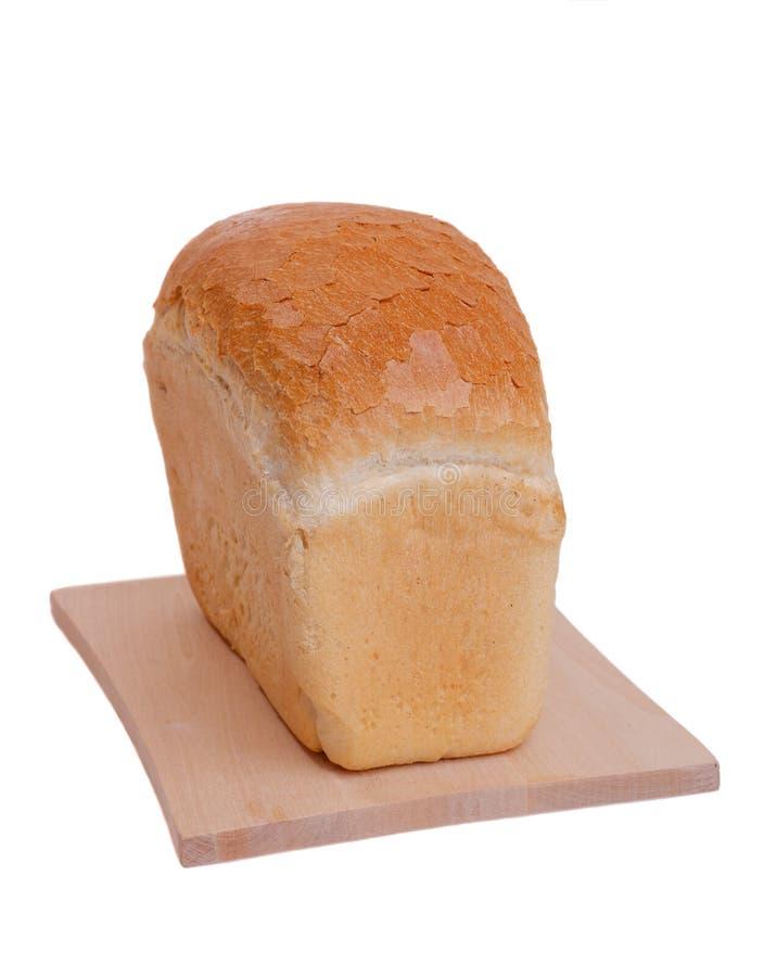 Brotlaib auf dem Schneidebrett lokalisiert auf weißem Hintergrund stockfoto