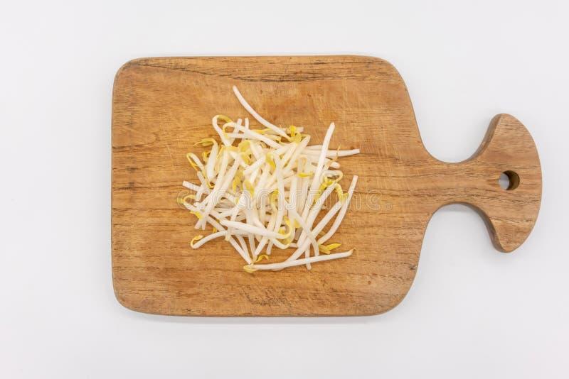 Broto de soja na placa de desbastamento de madeira isolada no branco foto de stock royalty free