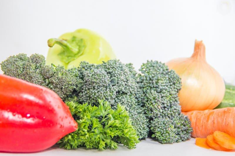 Brotos verdes dos brócolis e ervas frescas na tabela branca Composição do vegetariano foto de stock royalty free