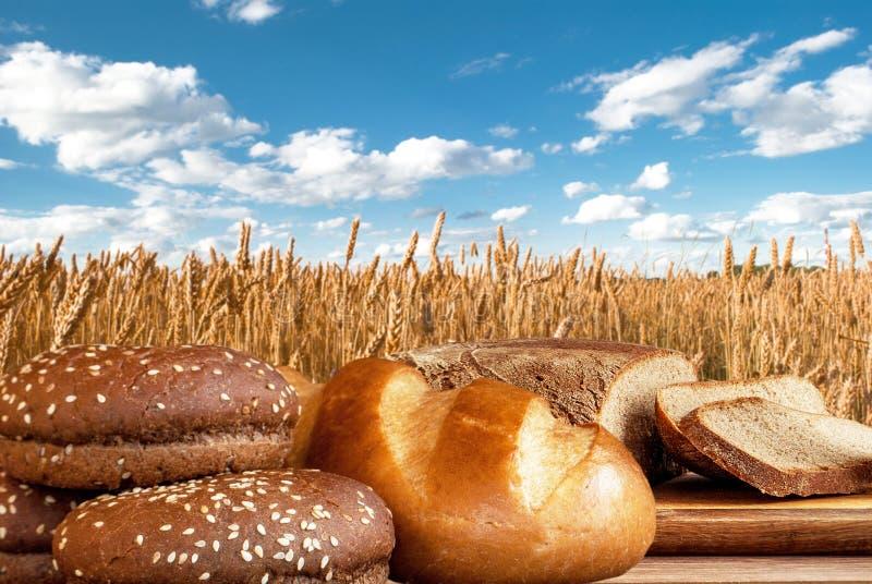 Brotprodukte auf dem Hintergrund eines Weizenfeldes lizenzfreie stockfotos
