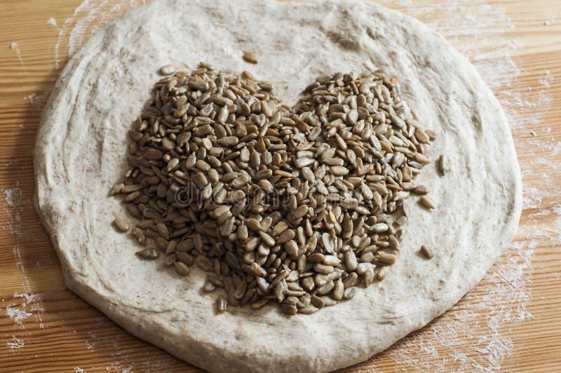 Brotteig mit den Samen, die ein Herz bilden stockfotos