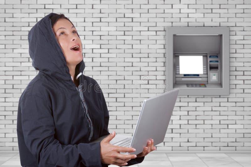Brottslig kvinnaen hacker som framme bär Hood On Using en bärbar dator av royaltyfria bilder