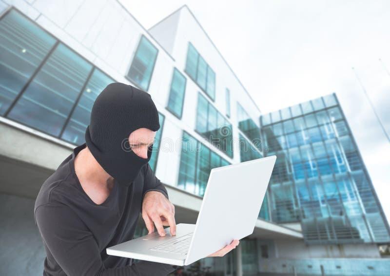 Brottslig man i balaclava på bärbara datorn framme av glass byggnad arkivfoto