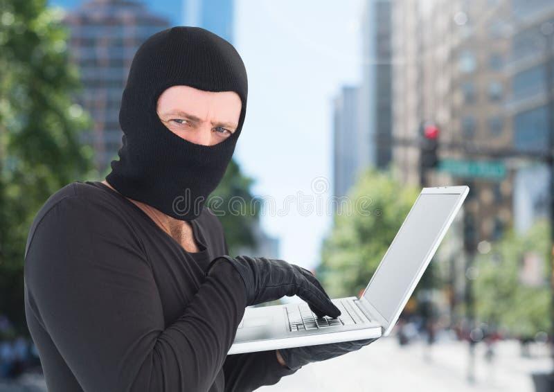 Brottslig man i balaclava på bärbara datorn framme av staden royaltyfria foton