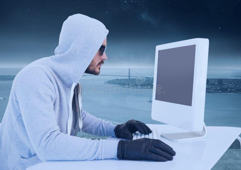 Brottslig man i huv på datoren framme av landskapet arkivbilder