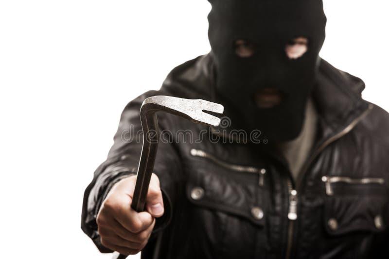 Brottslig tjuv- eller inbrottstjuvman i hållande crowb för balaclava eller för maskering royaltyfri foto