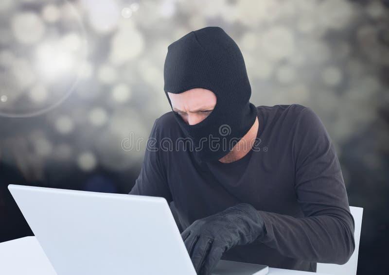 Brottsling i balaclava med bärbara datorn i mousserande ljus arkivfoto