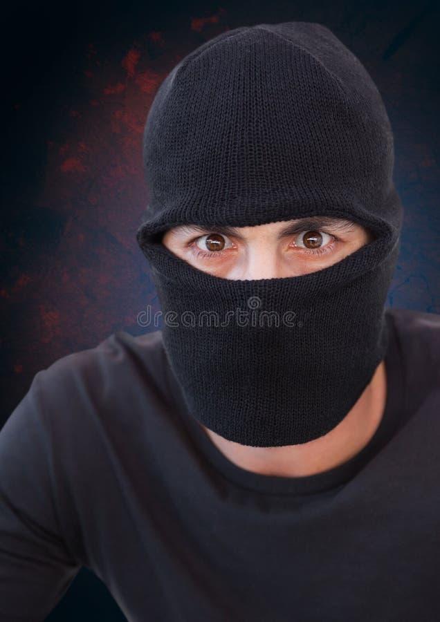 Brottsling i balaclava med blå bakgrund arkivbilder