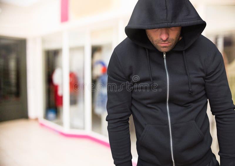 Brottsling i huv i supermarket fotografering för bildbyråer