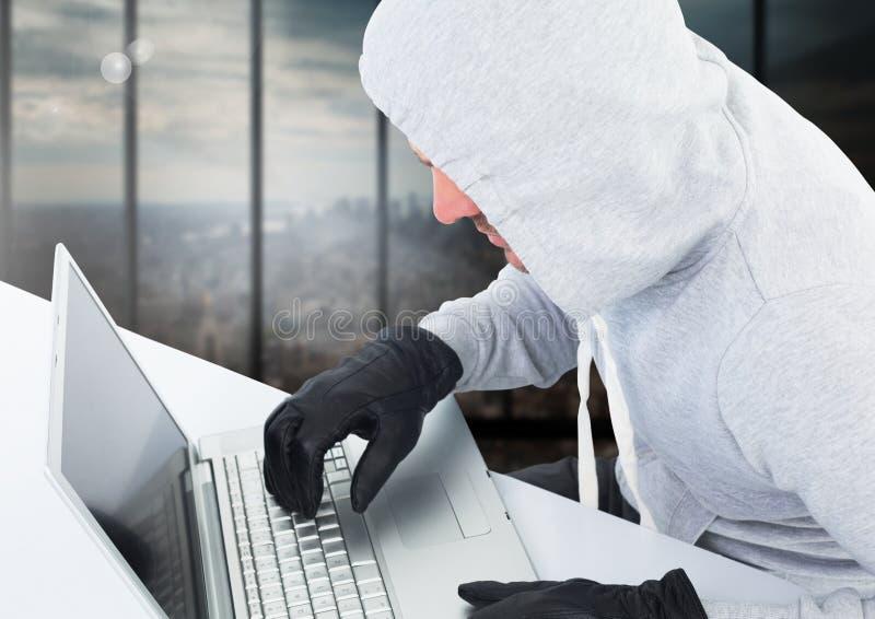Brottsling i huv med bärbara datorn som är främst av fönster arkivbilder
