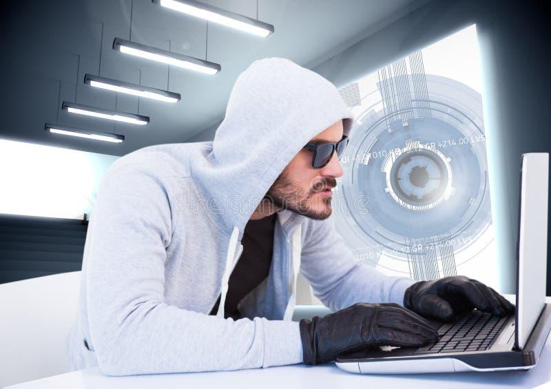 Brottsling i huv på bärbara datorn framme av manöverenheten arkivfoto