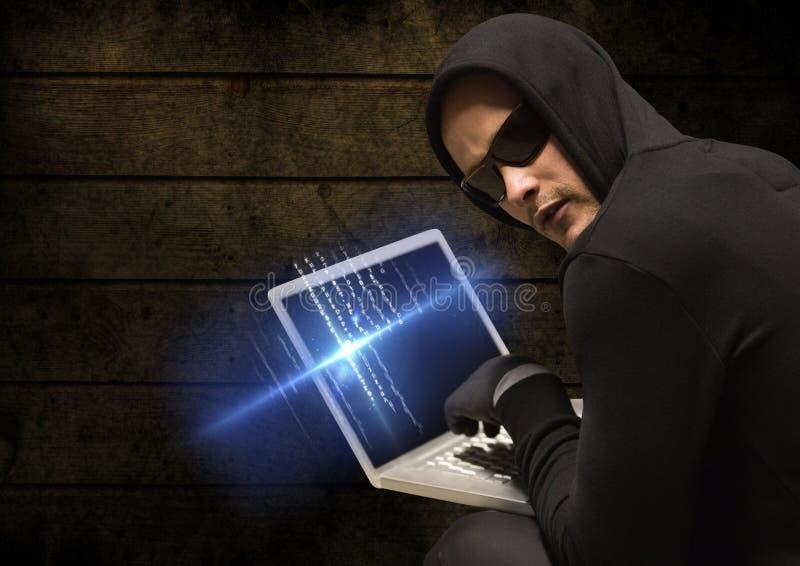Brottsling i huv på bärbara datorn framme av trä arkivfoton