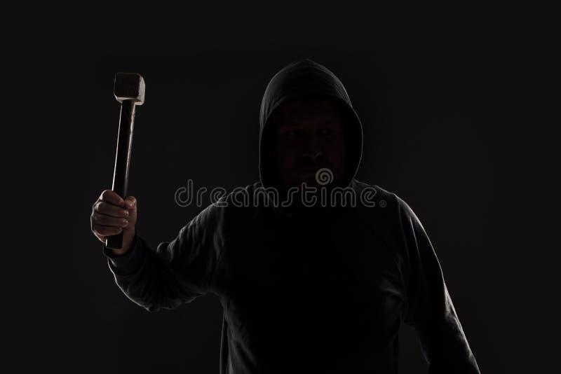 Brottsling i mörkerkläder och balaclava med hammaren arkivfoto