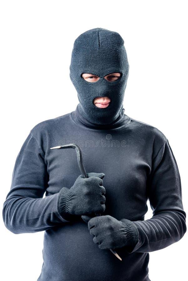 Brottsling med en kofot i händer i svart posera för balaclava arkivbild