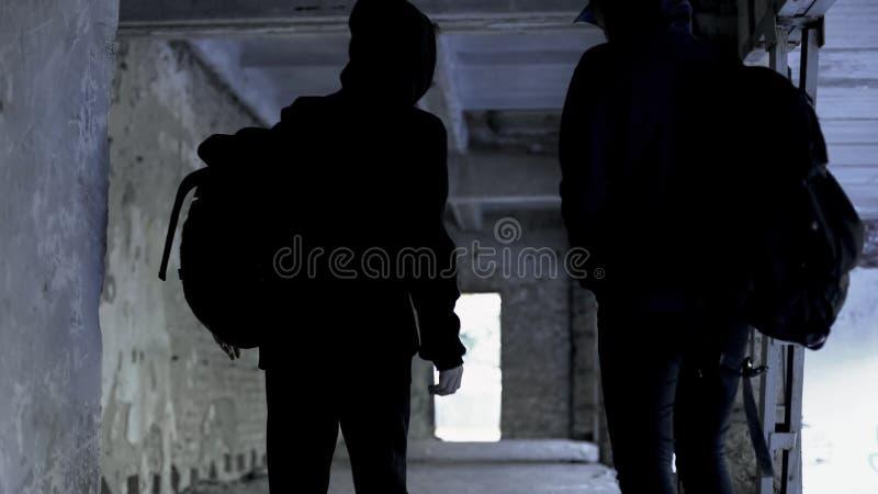 Brottslingar som bär svart gå i övergett hus, brotts- planläggning, komplott arkivbild