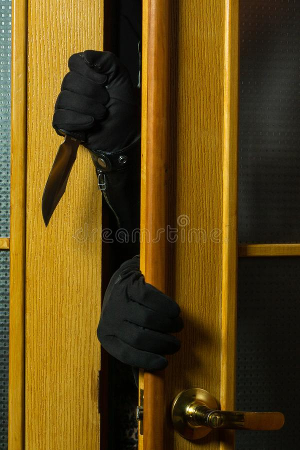 Brottslingen får in i lägenheten Mans händer i svarta handskar och en kniv arkivbilder