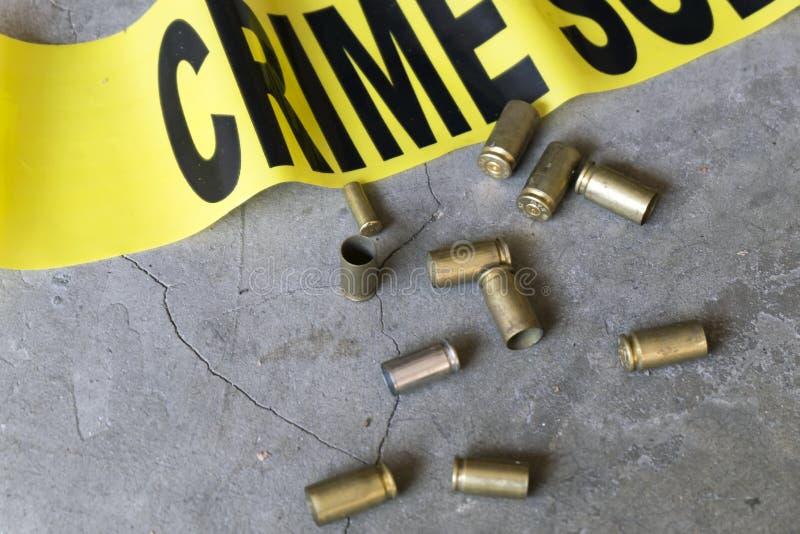 Brottsplats som är nära upp av casings för brottsplatsband- och mässingskula arkivfoto