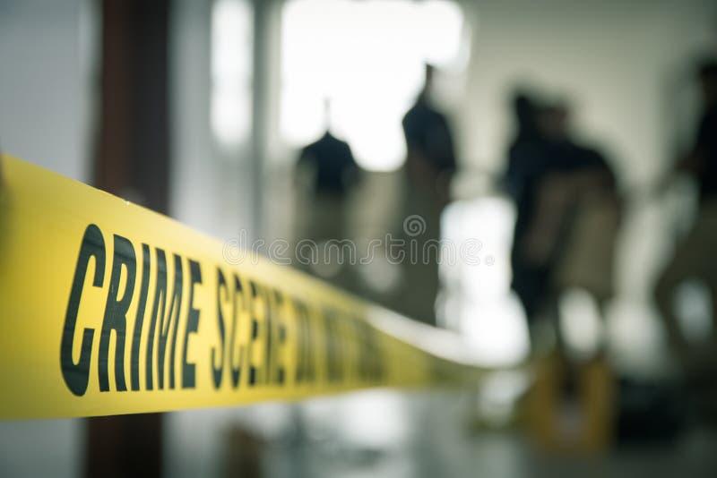 Brottsplatsband med suddig rättsmedicinsk rättsskipningbackgroun royaltyfria foton
