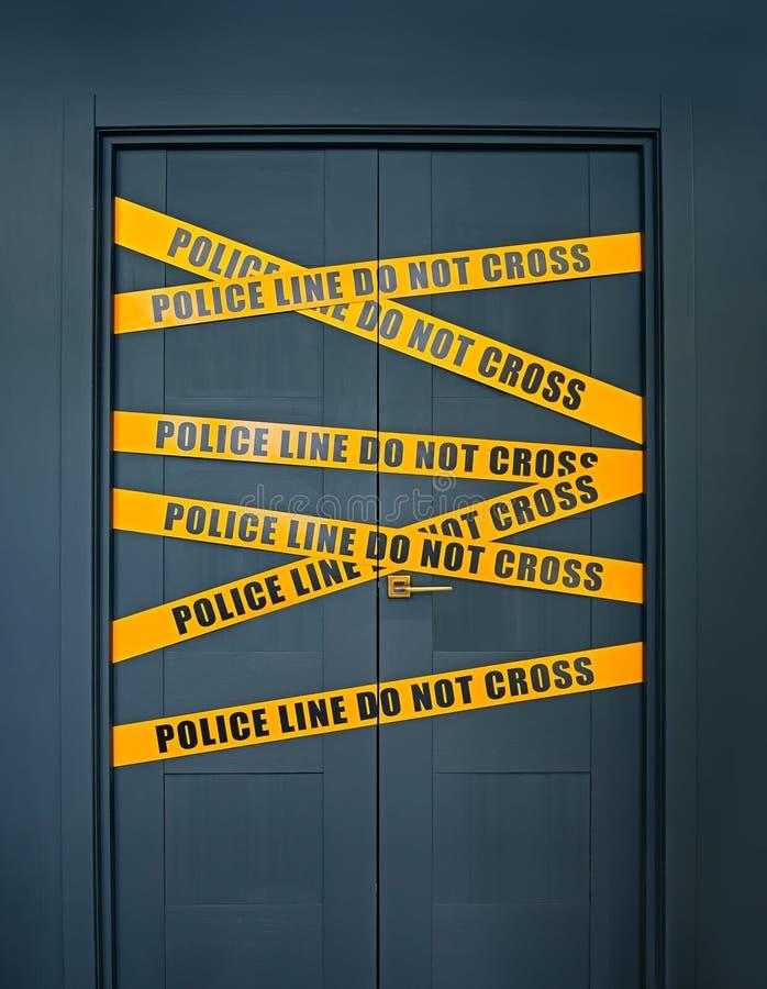 Brottsplatsen stängda dörren med den gula linjen för bandtextpolisen korsar inte arkivfoton