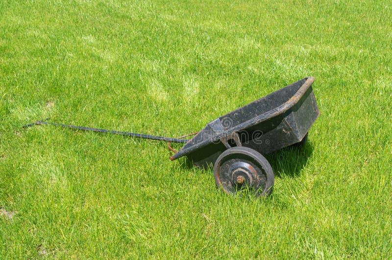 Brouette de roue rouillée sur une pelouse d'été photo stock