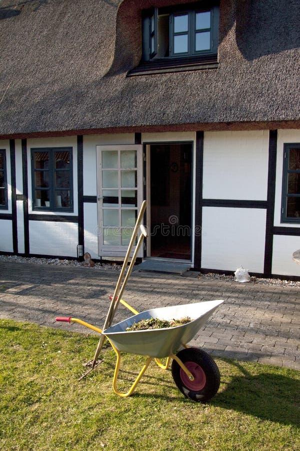 Brouette de roue sur l'herbe dans le jardin avec le râteau et la houe devant la maison à colombage romantique avec le toit de cha photographie stock libre de droits