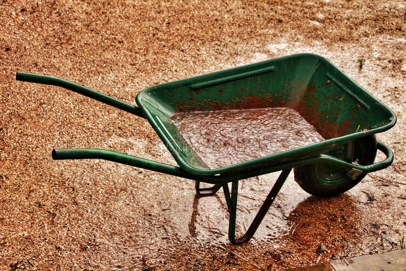 Brouette verte complètement de l'eau par la pluie images libres de droits