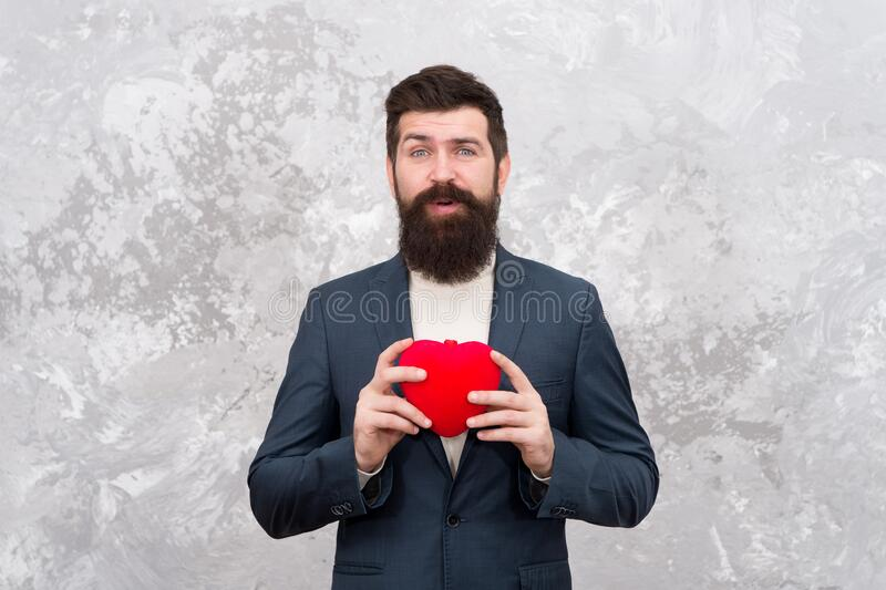 Brought present. Bearded man hold red heart. Valentine present. Hipster give present abstract background. Present for stock images