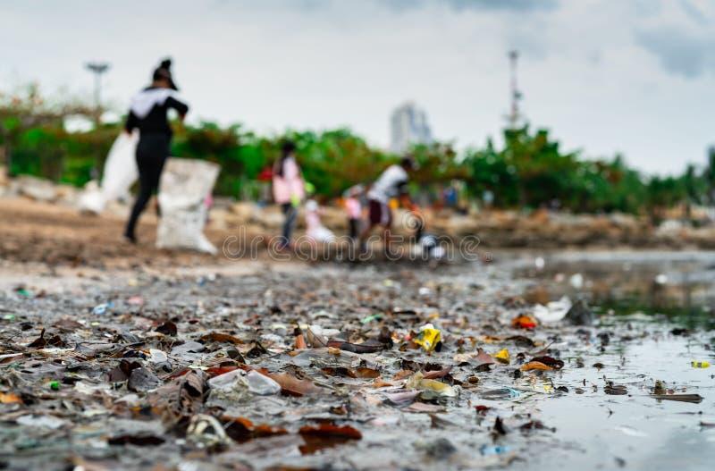 Brouillé des volontaires rassemblant des déchets Pollution d'environnement de plage Volontaires nettoyant la plage Rangement des  images stock