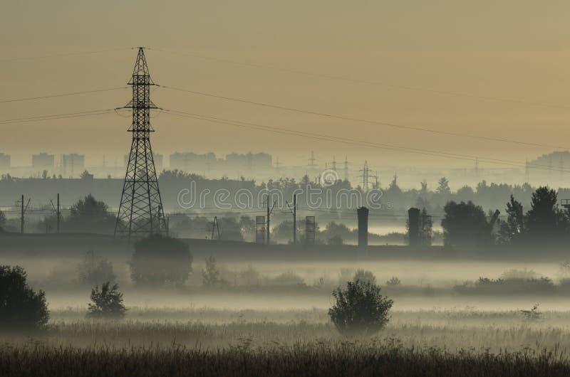 Brouillard au-dessus des champs et de la tour des lignes électriques photos libres de droits
