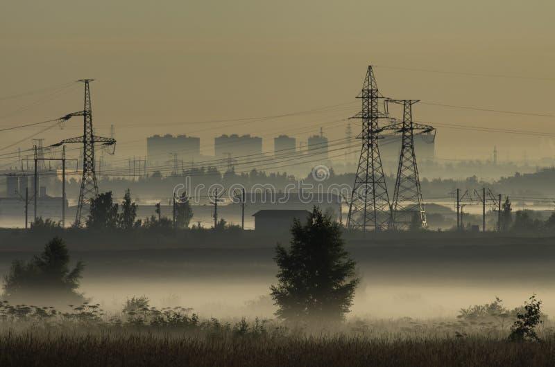 Brouillard au-dessus des champs et des tours des lignes électriques photo libre de droits