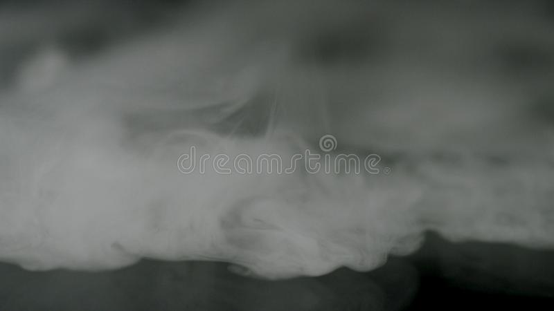 brouillard blanc sur le fond noir, effet fumeux Longueur courante Nuages de fum?e brouill?s recouverts sur le fond noir images stock