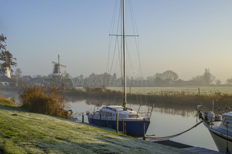 Brouillard, moulins à vent et bateaux sur une rivière images stock