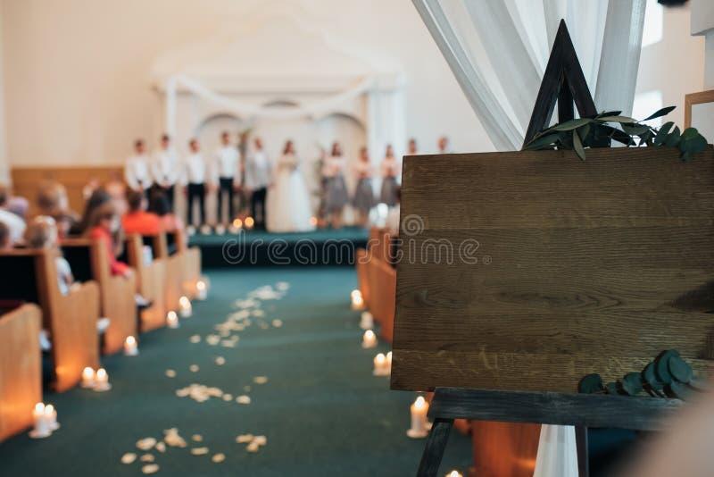 Brouillez la cérémonie de mariage dans l'église Dans le premier plan tient un chevalet en bois avec l'espace pour le texte photos libres de droits