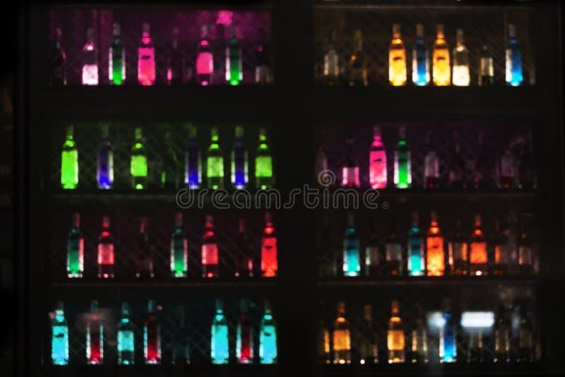 Brouillez la lampe au néon rougeoyante de la bouteille potable d'alcool dans la barre ou du bar pour le fond foncé de partie de n images stock