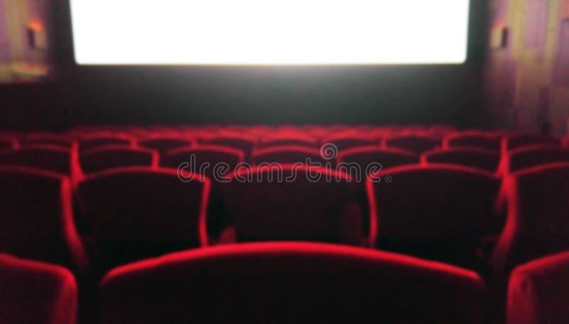 Brouillez la salle de cinéma avec les chaises rouges utilisées comme calibre image libre de droits