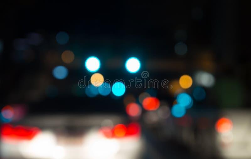 Brouillez le bokeh abstrait du fond de lumière de nuit de ville de rue image stock