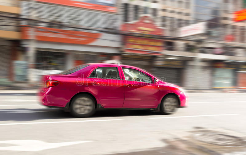 Brouillez le concept de mouvement du taxi rose sur la route images stock