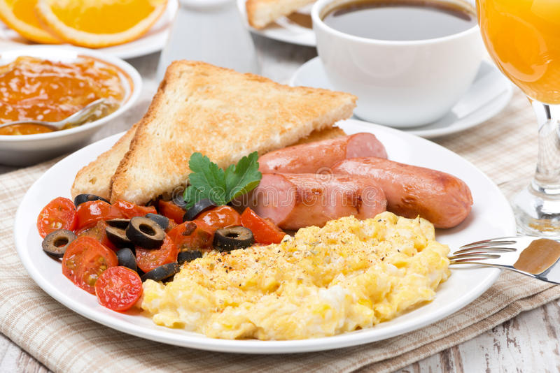 Brouillez les oeufs avec les tomates, la saucisse et le pain grillé pour le petit déjeuner photos stock