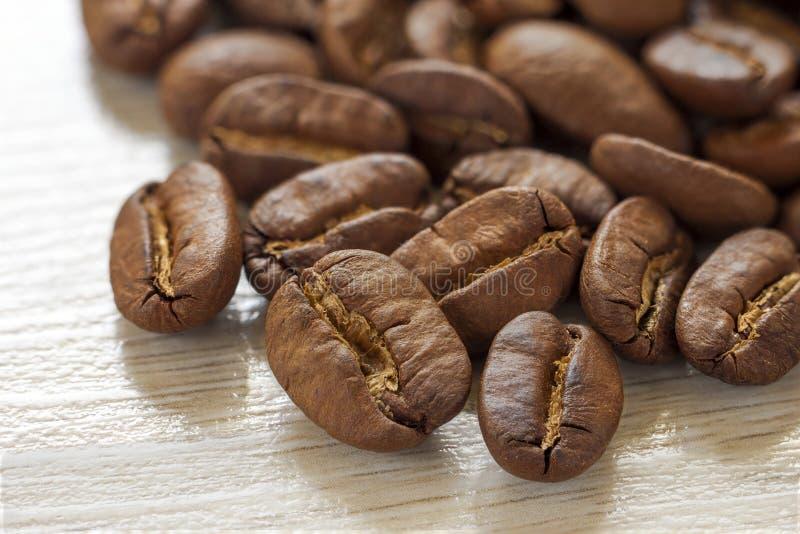 Broun-Kaffeebohnen lokalisiert auf strukturiertem hölzernem Hintergrund mit stockbilder