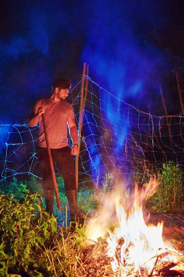 Broussaille brûlante d'homme sur le feu, nettoyage saisonnier du secteur de campagne, mode de vie de village image libre de droits