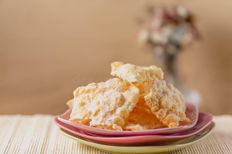 Broussaille croustillante crépitée de biscuits avec du sucre en poudre sur plats roses Bonbons d'un plat et d'un sucre en poudre image stock