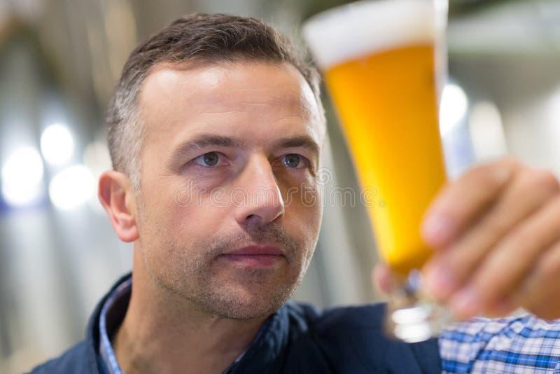 Brouwer die bier controleren bij brouwerijfabriek royalty-vrije stock afbeelding