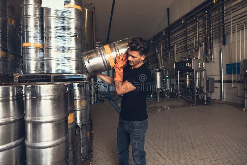 Brouwer met vaatje bij het pakhuis van de brouwerijfabriek stock afbeelding