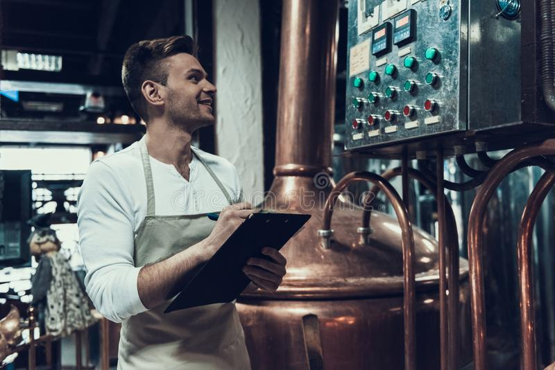 Brouwer Standing dichtbij Apparaten in Moderne Brouwerij royalty-vrije stock foto's