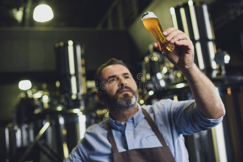 Brouwerijarbeider met glas bier royalty-vrije stock afbeeldingen